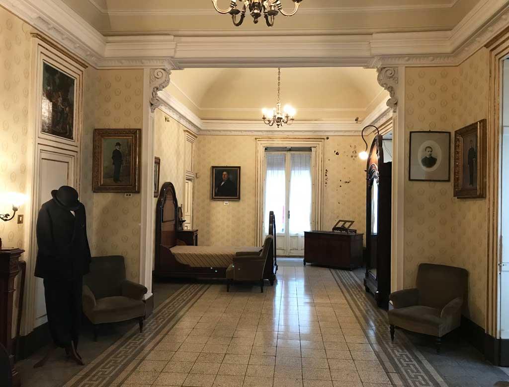 Museo-casa-di-giovanni-verga-stanza-da-letto-abiti-poltrone-tappezzeria-gialla