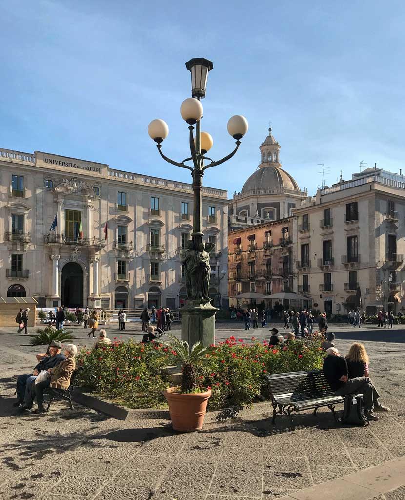 piazza-delluniversita-catania-persone-sedute-su-una-panchina-lampione
