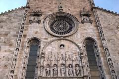 Duomo-di-como-facciata-statue-pietra-rosone-cielo-azzurro