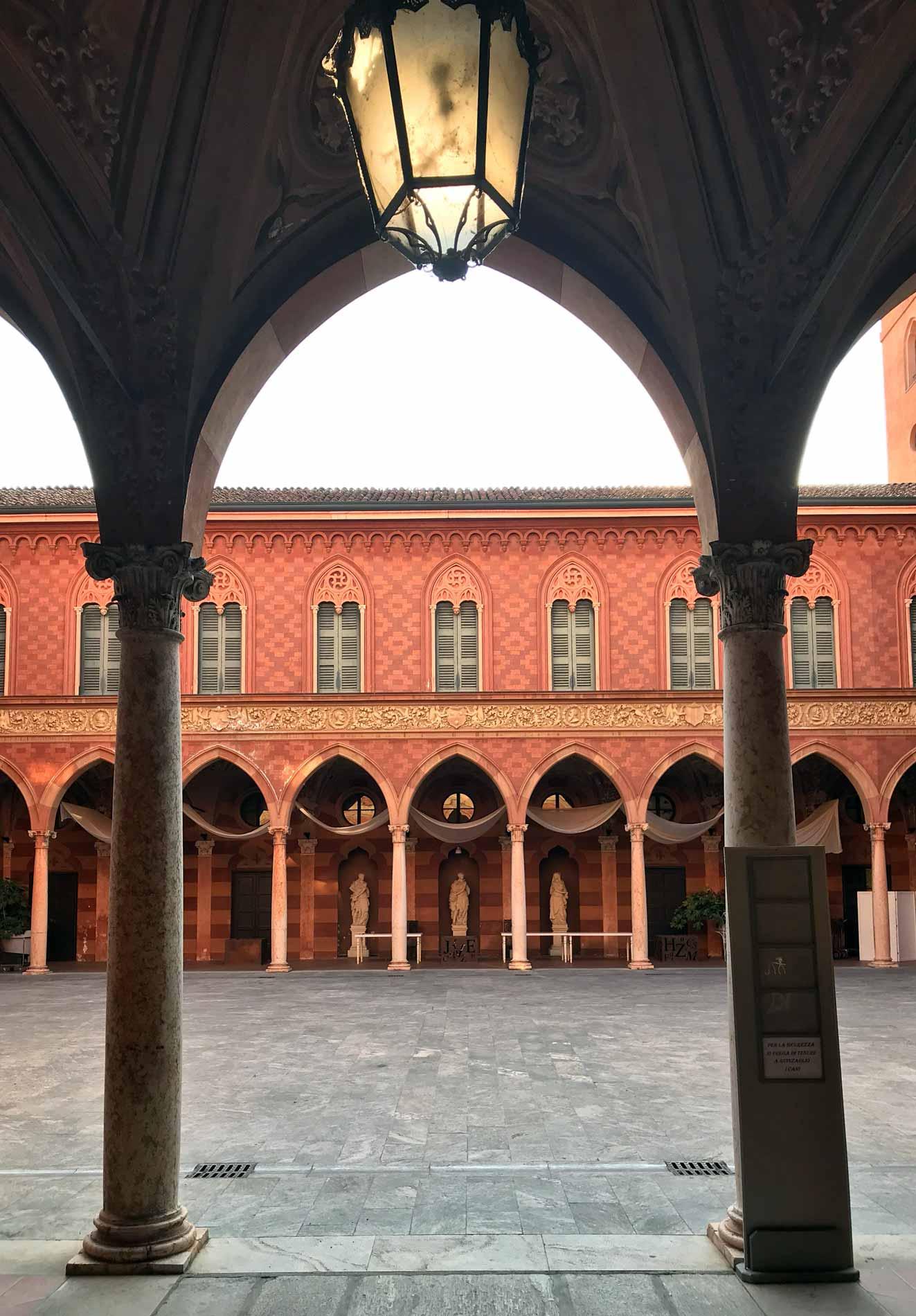 Palazzo-Trecchi-Cremona-via-trecchi-cortile-interno-arcate-facciata-rossa