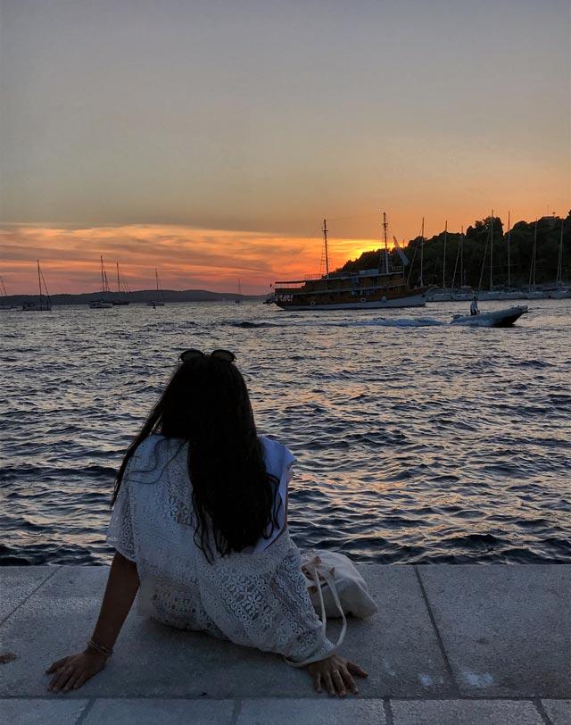 hvar-croazia-ragazza-guarda-il-tramonto-sul-mare
