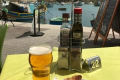 Marsaxlokk-Malta-pastizzi-birra-tavolino-mare-cielo