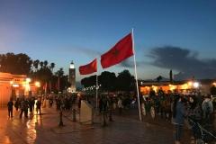 Piazza-Jamaa-el-fna-marrakech-ora-blu-luci-bandiere-marocco-persone-koutoubia
