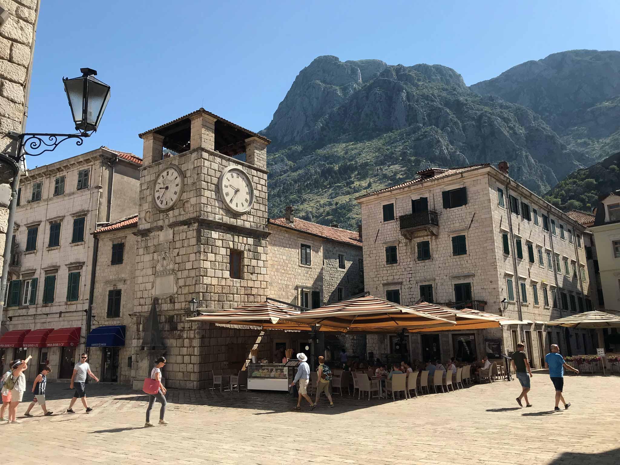 Cattaro-Montenegro-Piazza-dArmi-Torre-dellOrologio-sole-montagna-persone-lampione