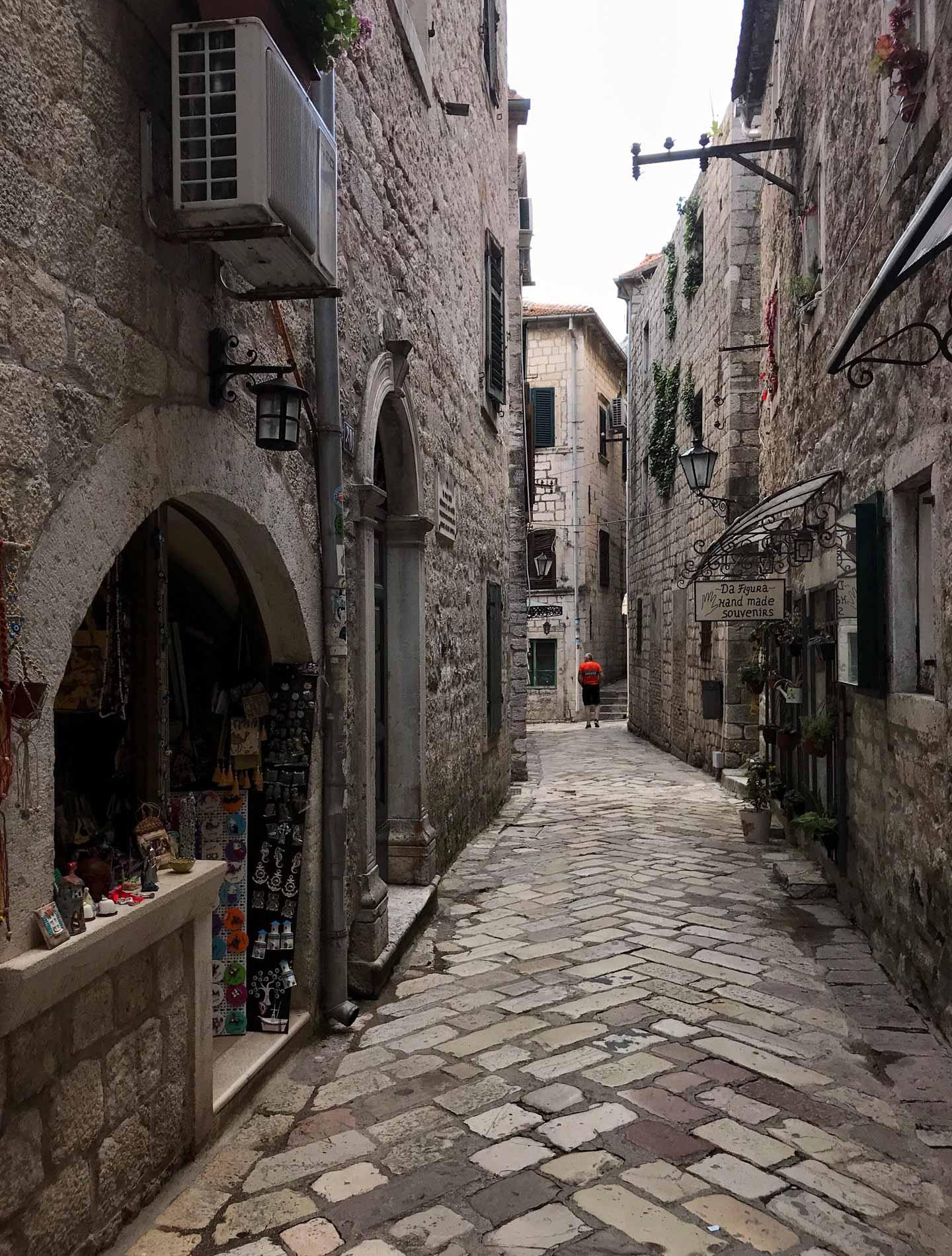 Kotor-Montenegro-via-Ulica-2-case-fontanella-muri-in-pietra-negozietto