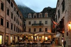 Kotor-Montenegro-Piazza-dArmi-luci-sera-lampioni-tavoli-allaperto-case-atmosfera-magica