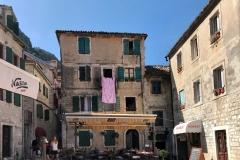 Kotor-Montenegro-Piazza-delle-Erbe-palazzo-lenzuolo-rosa-tavolini