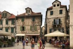 spalato-piazza-della-frutta-turisti-camminano-davanti-alle-case-tradizionali