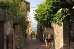 Brunate-como-strada-in-salita-tra-le-case-ciclista-passante