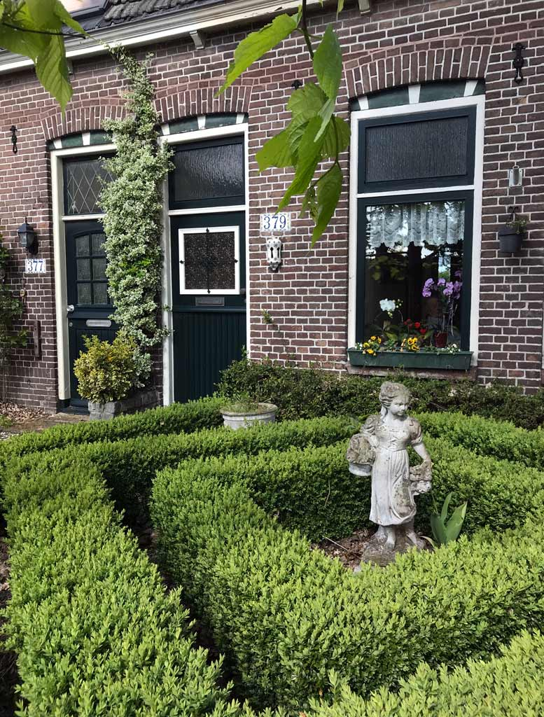 Vogelenzag-olanda-giardino-di-una-casa-con-statua-e-siepi-curate