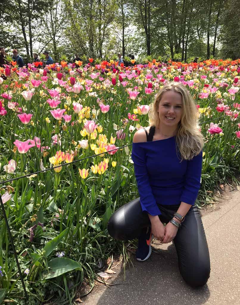 turista-bionda-in-posa-davanti-ai-tulipani-di-parco-keukenhof