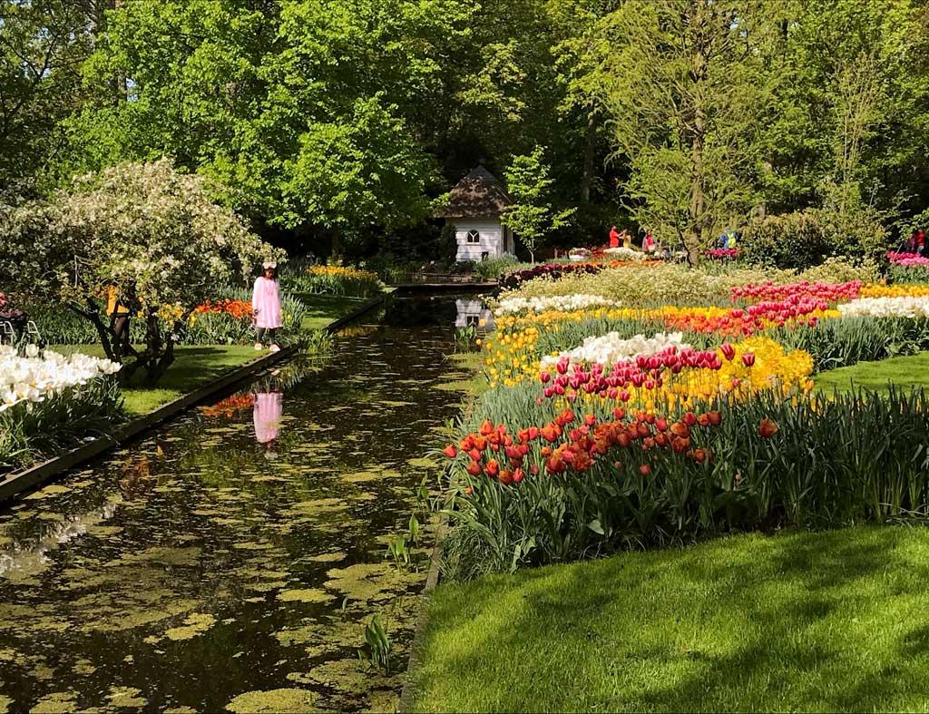 bambina-vicino-a-un-canale-e-ai-tulipani-di-parco-keukenhof-in-olanda