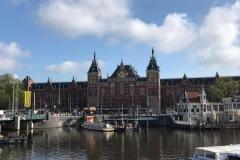 stazione-di-Amsterdam-riflessa-nel-canale-con-cielo-azzurro